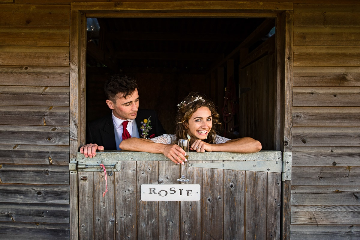bride and groom pose in horse stable