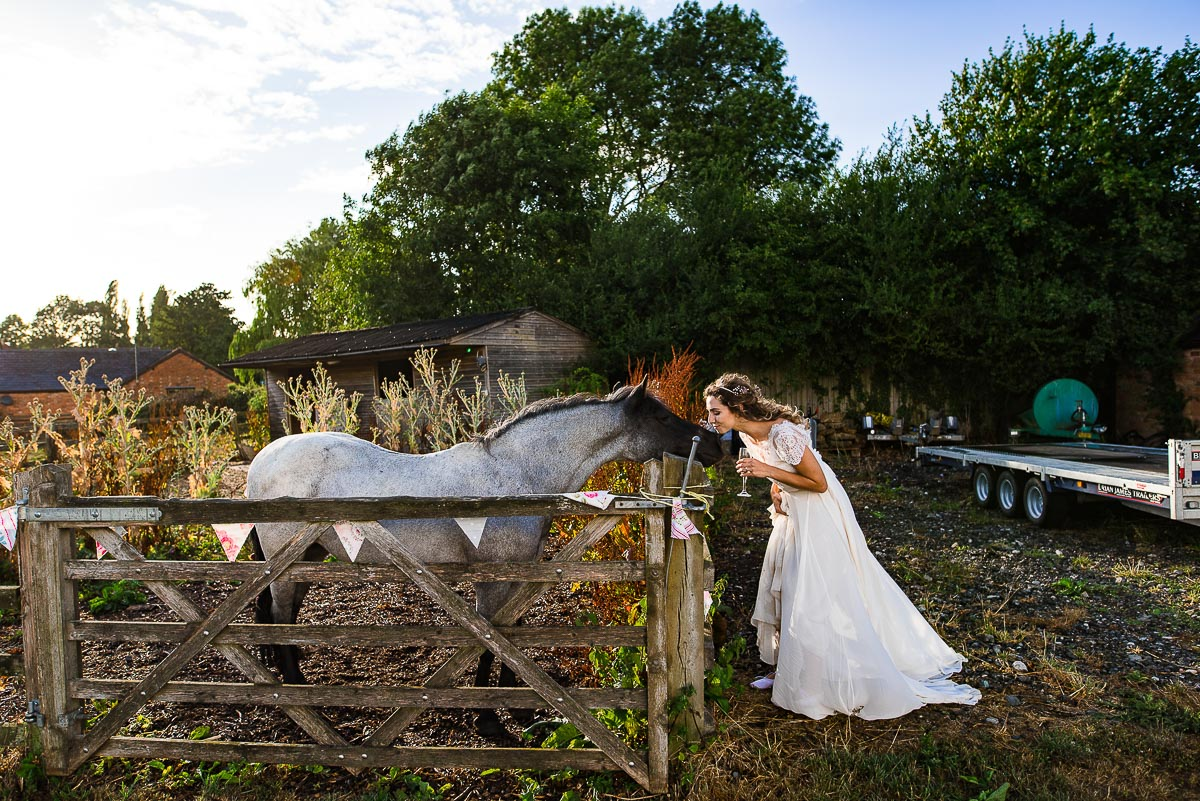 bride greets horse in country stable
