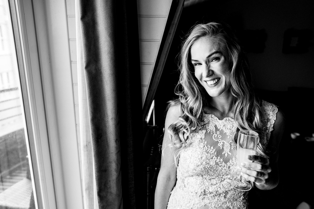 bride poses with drink by window portrait