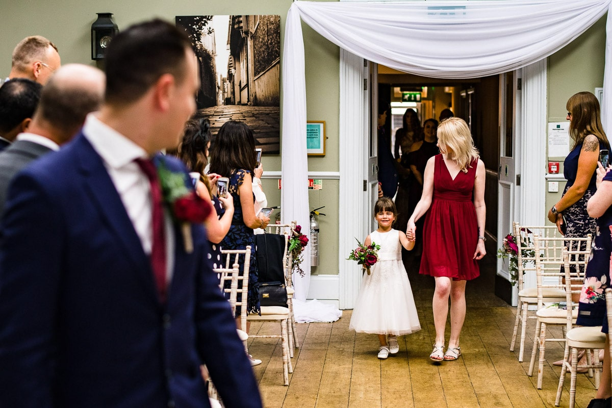 groom watches as bridesmaids appear from back of aisle