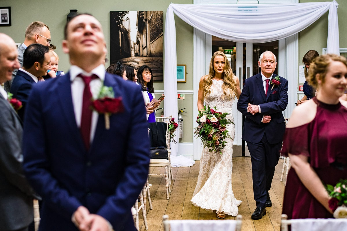 father of bride walks bride down aisle