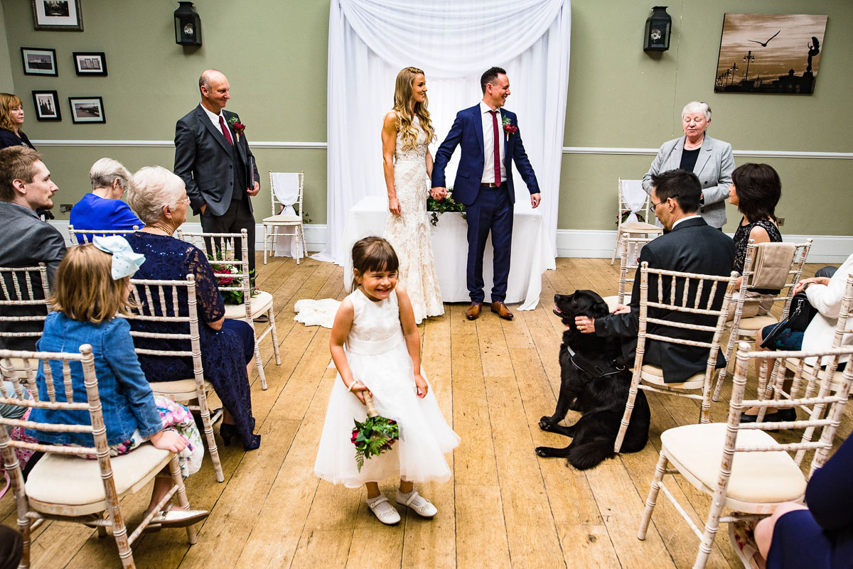 flower girl grins as bride and groom leave