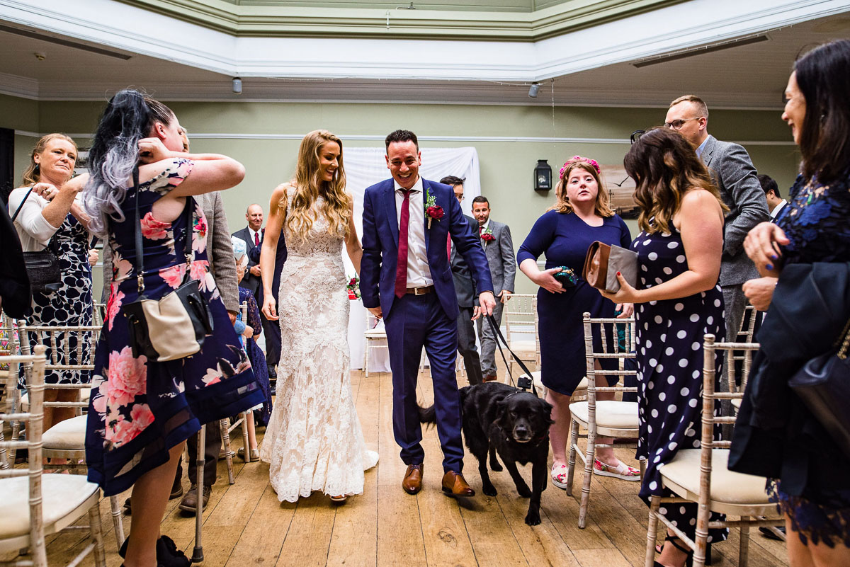 bride and groom walk away from alter with dog