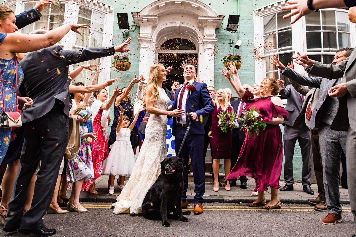wedding guests celebrate wedded couple with confetti