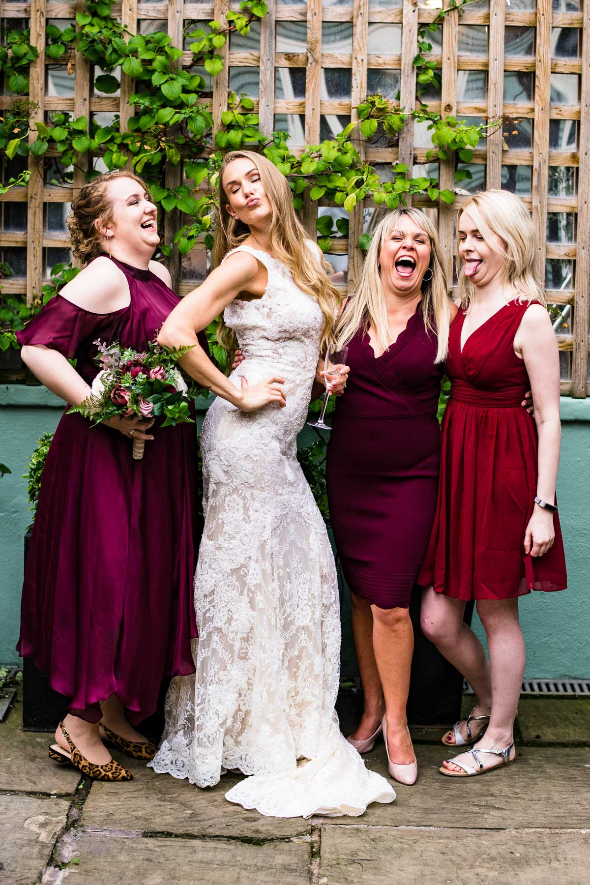 bride and bridesmaids laugh and pose together