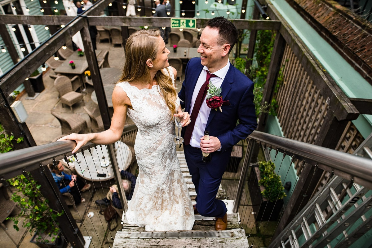 bride and groom pose on stairs with drinks