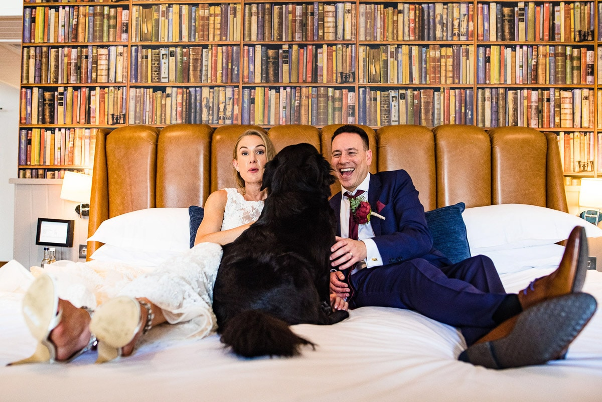 bride groom and dog lay on hotel bed