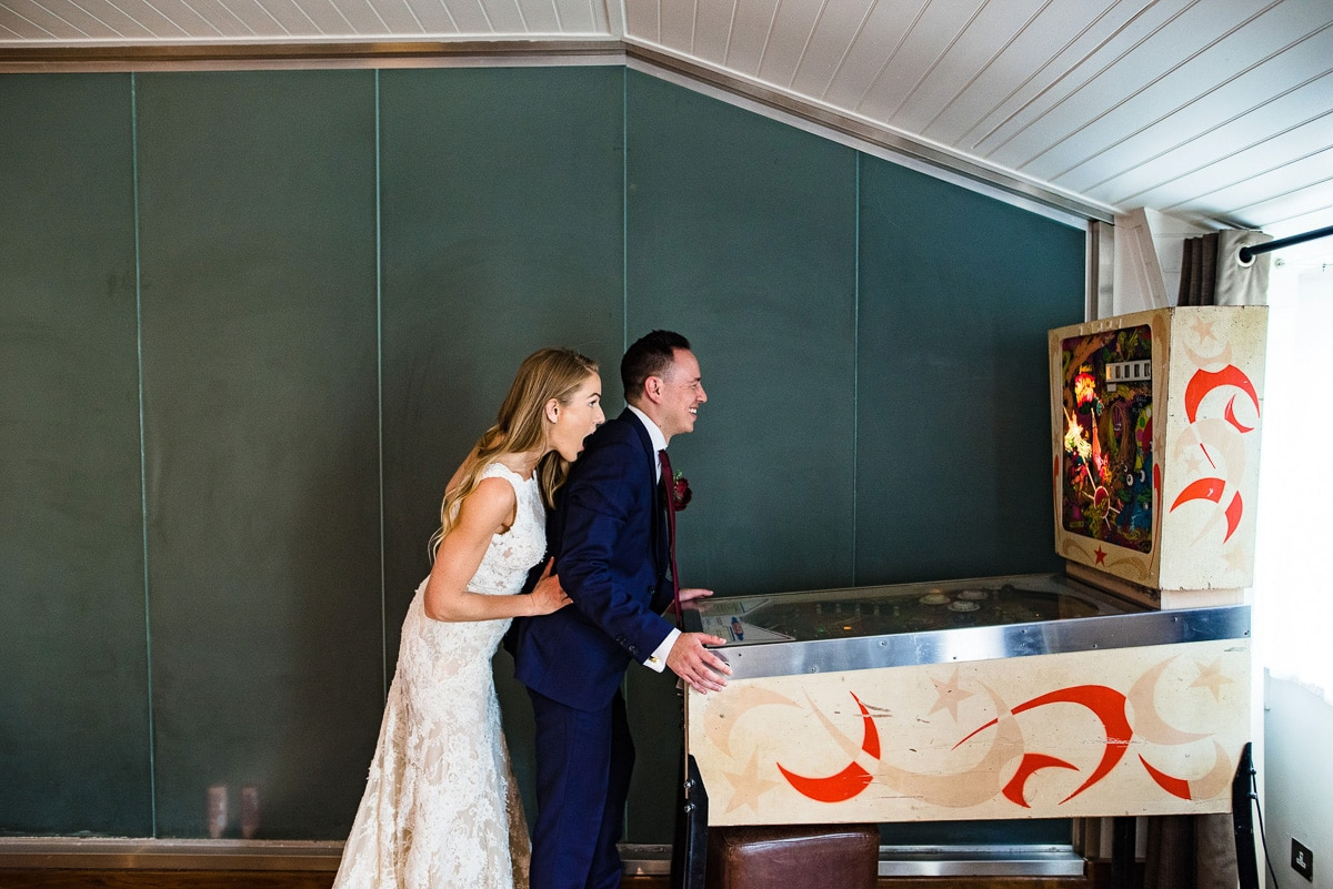 bride and groom play pinball in brighton hotel lobby