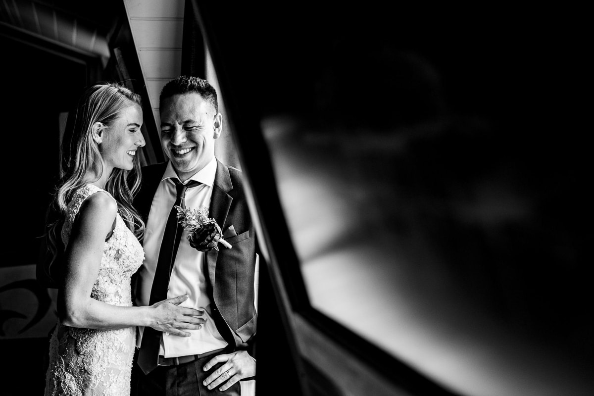 bride and groom laugh and smile by window portrait