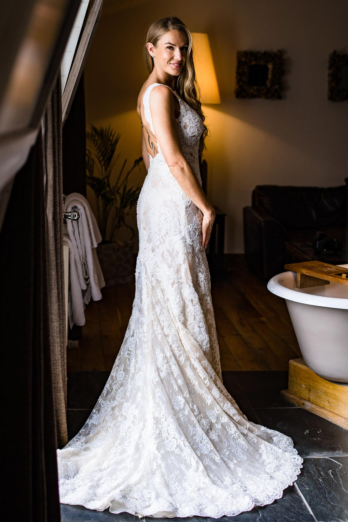 bride admires elegant lacy dress in mirror