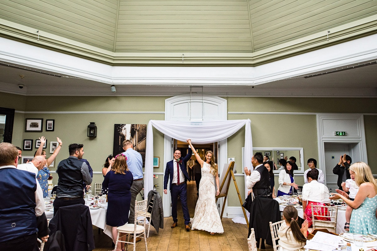 bride and groom enter dining room hand in hand